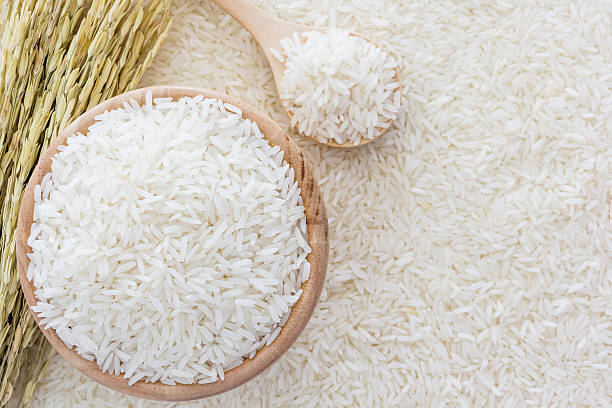 White rice in bowl and a bag, a wooden spoon and rice plant on white rice background, Top view with copy space